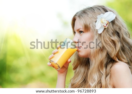 Young happy smiling woman drinking orange juice outdoor