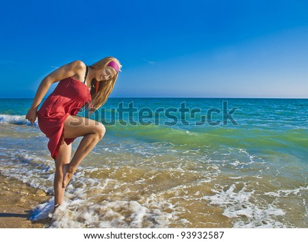 Young happy smiling woman having fun in the sea blue water near the seacoast