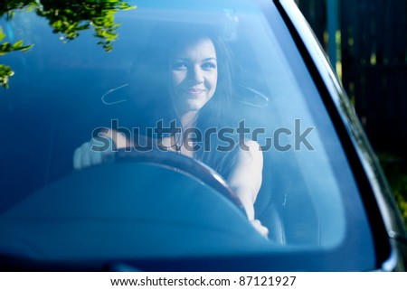 Young happy smiling woman in black car