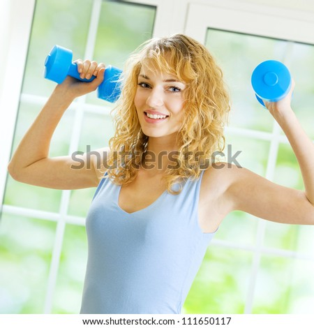 Young happy smiling woman in sportswear, doing fitness exercise with dumbbells, indoors