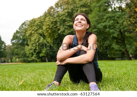 Young happy smiling woman looking up siting in grass
