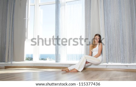 young happy smiling woman next to big window at home / hotel