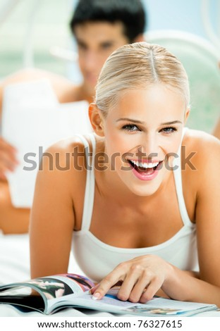 Young happy smiling woman reading magazine at bedroom