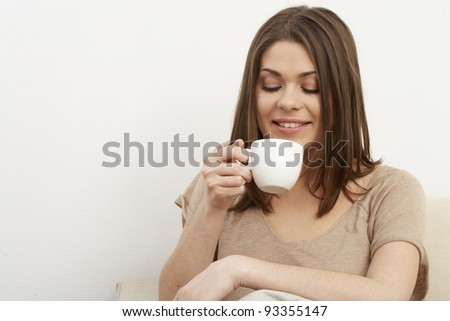 Young happy smiling woman sitting on sofa in bright room. Casual style portrait