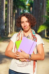 Young happy smiling woman (student, teacher) holding books and notebooks outside in the park