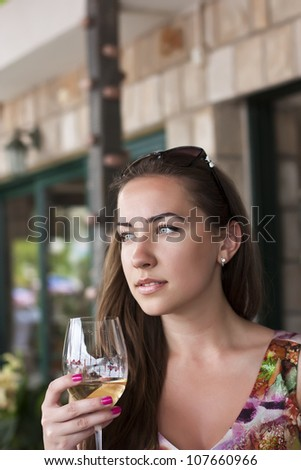 Young happy smiling woman, with glass of whitewine at restaurant