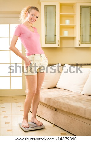 Young happy smiling woman with scales at home