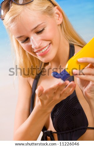 Young happy smiling woman with sun-protection cream on beach. Focus on woman.