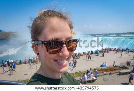 Young happy smiling woman with sunglasses on beautiful sunny springtime morning at Niagara Falls.  People & tourists in background see, hear, and feel the power of the Falls.