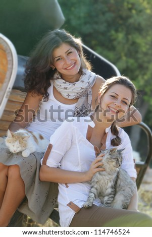 young happy smiling women with cats on natural background