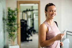 Young happy sportswoman using mobile phone in a lobby at the gym and looking at camera.