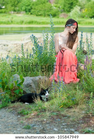 Young happy teenage girl sitting on river bank among flowers and holding black cat on lead