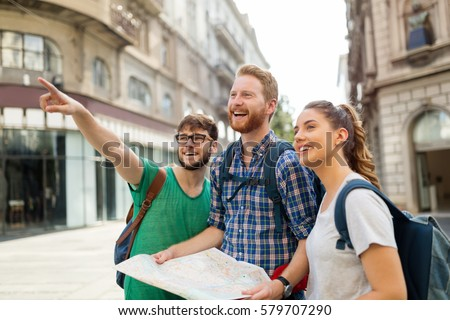 Young happy tourists holding map sightseeing in city #579707290