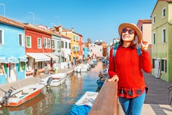 young happy traveler woman posing among colorful houses on Burano island, Venice. Tourism in Italy concept