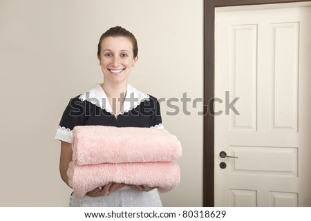 young happy uniformed maid carrying towels