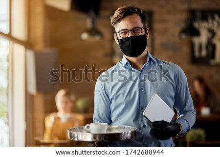 Young happy waiter wearing protective face mask while working in reopened cafe after coronavirus epidemic.