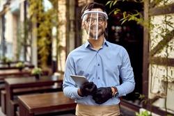Young happy waiter wearing visor and protective gloves while standing at outdoor cafe and looking at camera.