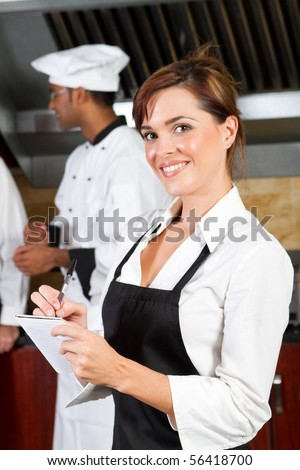 young happy waitress in restaurant kitchen with chefs behind