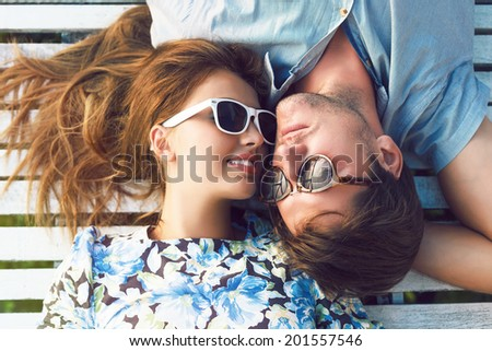 Young happy woman and her handsome boyfriend laying outdoor in wooden white floor, wearing vintage styled clothes and sunglasses.