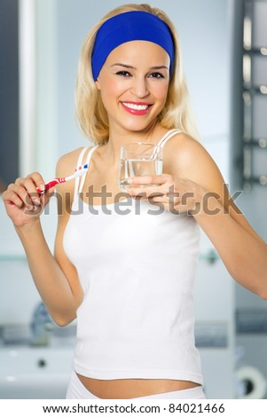 Young happy woman bruhing teeth
