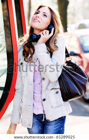 young happy woman calling from public phone, outdoor shot - stock photo