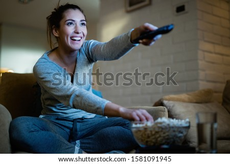 Young happy woman changing channels with remote control while watching TV and eating popcorn in the evening at home.
