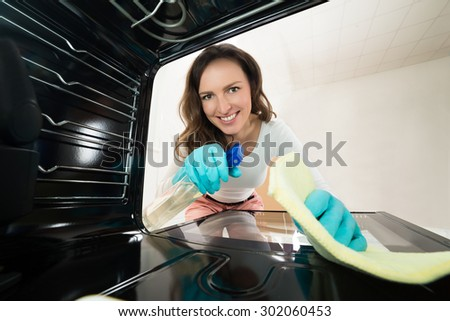 Young Happy Woman Cleaning View From Inside The Oven