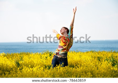 Young happy woman dancing in yellow flowers