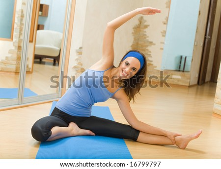 Young happy woman doing fitness exercises at home