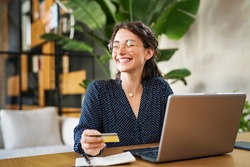 Young happy woman doing shopping online with laptop. Portrait of excited woman holding credit card and buy on an e-commerce site. Beautiful laughing girl paying online bills using debit card.
