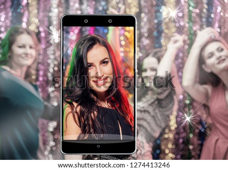 Young happy woman enjoying nightlife and dancing, conceptual image with a smartphone
