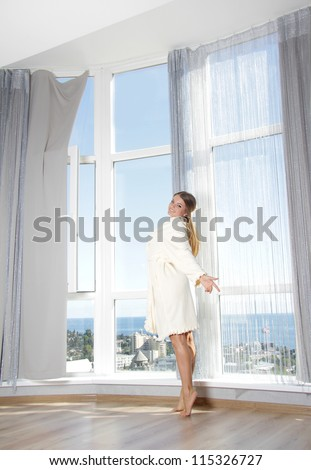 young happy woman enjoying sea view in hotel / room next to big window