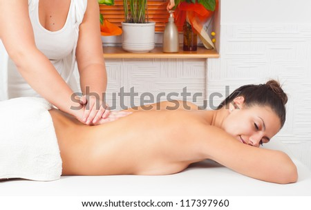 Young happy woman enjoying the massage in massage salon.