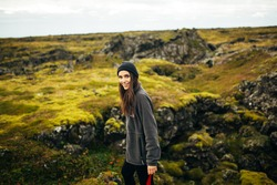 Young happy woman enjoying the view of the moss covered meadows in Iceland.Arctic circle wild nature adventure.Nature connection.Female wearing comfortable hiking clothes.Travelling and camping