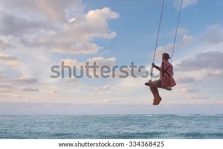 Young happy woman having fun on swing #334368425