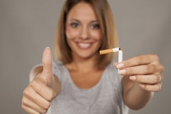 young happy woman holding a broken cigarette and showing thumbs up