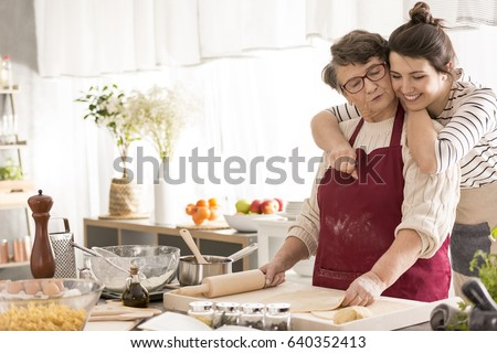 Young happy woman hugging her grandma cooking in a kitchen