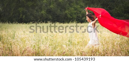 Young happy woman in a wheat field running with red fabric.