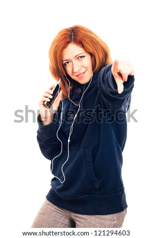 Young happy woman in blue hoodie holding smartphone, listening music and pointing at you, isolated on white background.