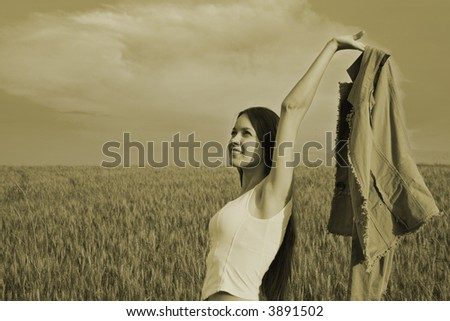 Young happy woman in field. Sepia.