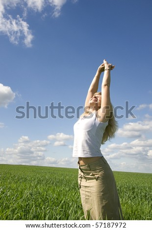 Young happy woman in field under blue sky