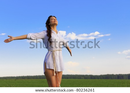 Young happy woman in green field, evening light