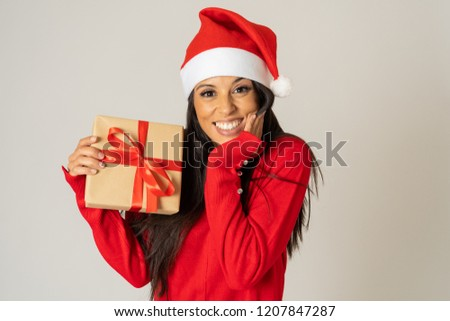 Young happy woman in red sweater and hat looking excited showing Christmas gift recycled paper isolated on grey background in shopping Christmas holidays shopping happiness celebration concept. stock photo