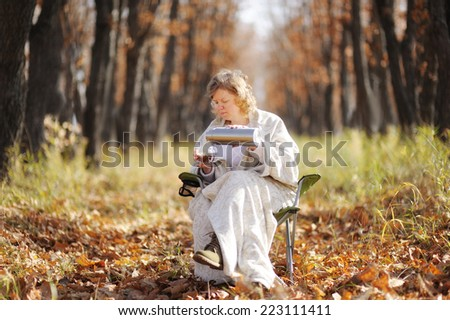 Young happy woman in the autumn sitting on a chair, wrapped in a blanket against the cold. poured from a thermos of hot tea, drink it. Peaceful life. Trees with falling leaves