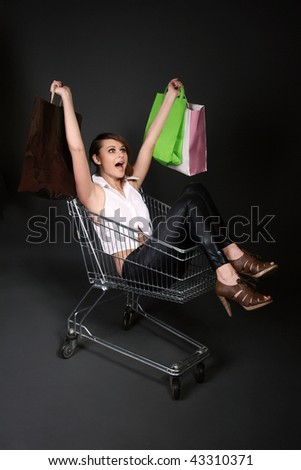 Young happy woman in the shopping cart with shopping bags
