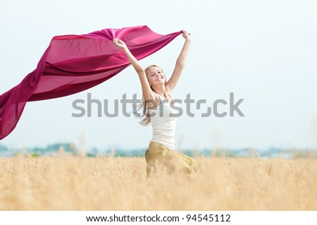Young happy woman in wheat field with fabric. Summer picnic