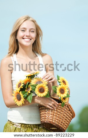 Young happy woman in wheat field with sunflower. Summer picnic