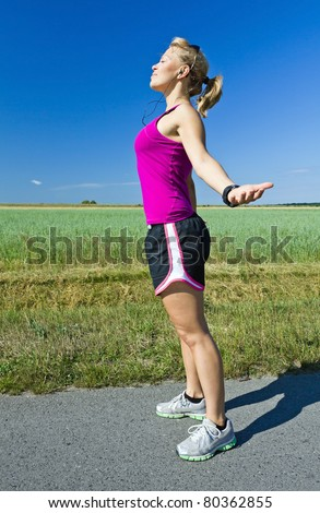 Young happy woman jogging relaxing after running, arms outstretched. Motivation and Inspiration Fitness Concept. Blue sky and green country landscape. Asphalt road on green village fields.