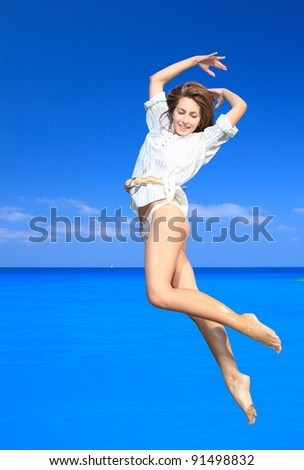 Young happy woman jumping on a beach