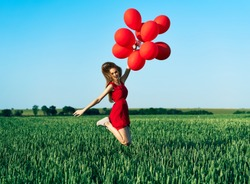 Young happy woman jumping with red balloons on green summer field. Fun, happiness, freedom, celebration concept